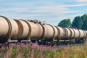 A train carrying liquid fuel passes through a prairie landscape