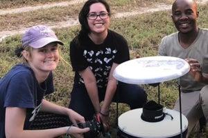 Three students around a mosquito trap