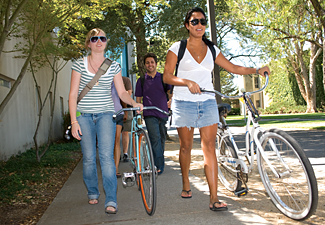 students walking there bikes along the sidewalk
