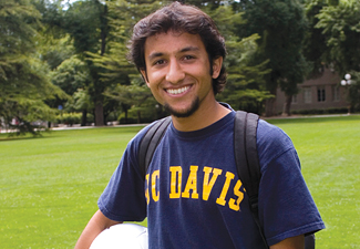 A smiling male student holding a soccer ball on the quad