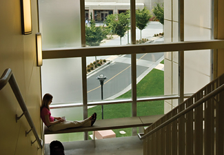 student reading and sitting in stairwell that overlooks part of campus