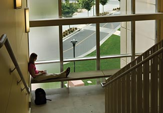 student in front of large window overlooking campus