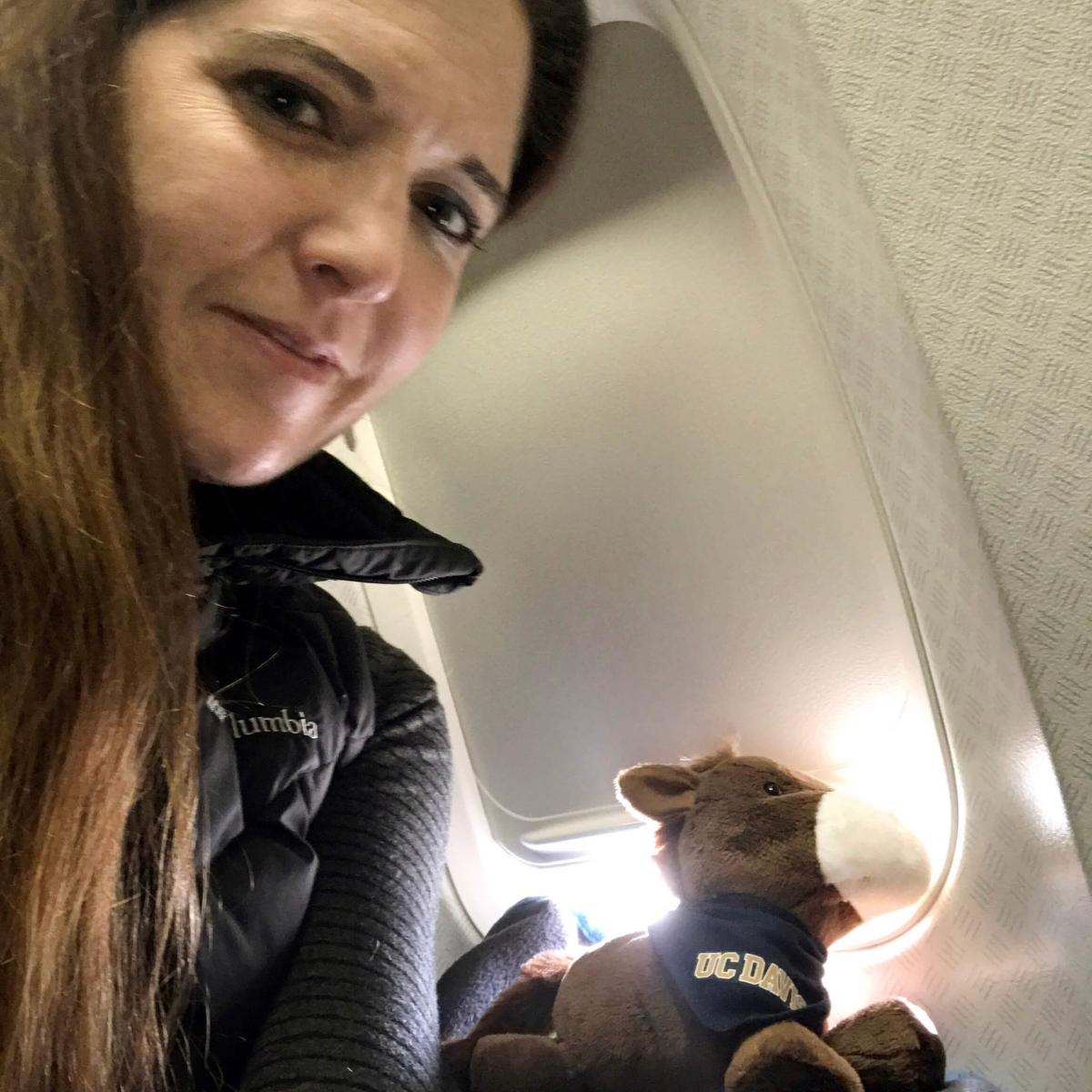 Jamie Peyton, UC Davis researcher, sits on a plane with a stuffed horse