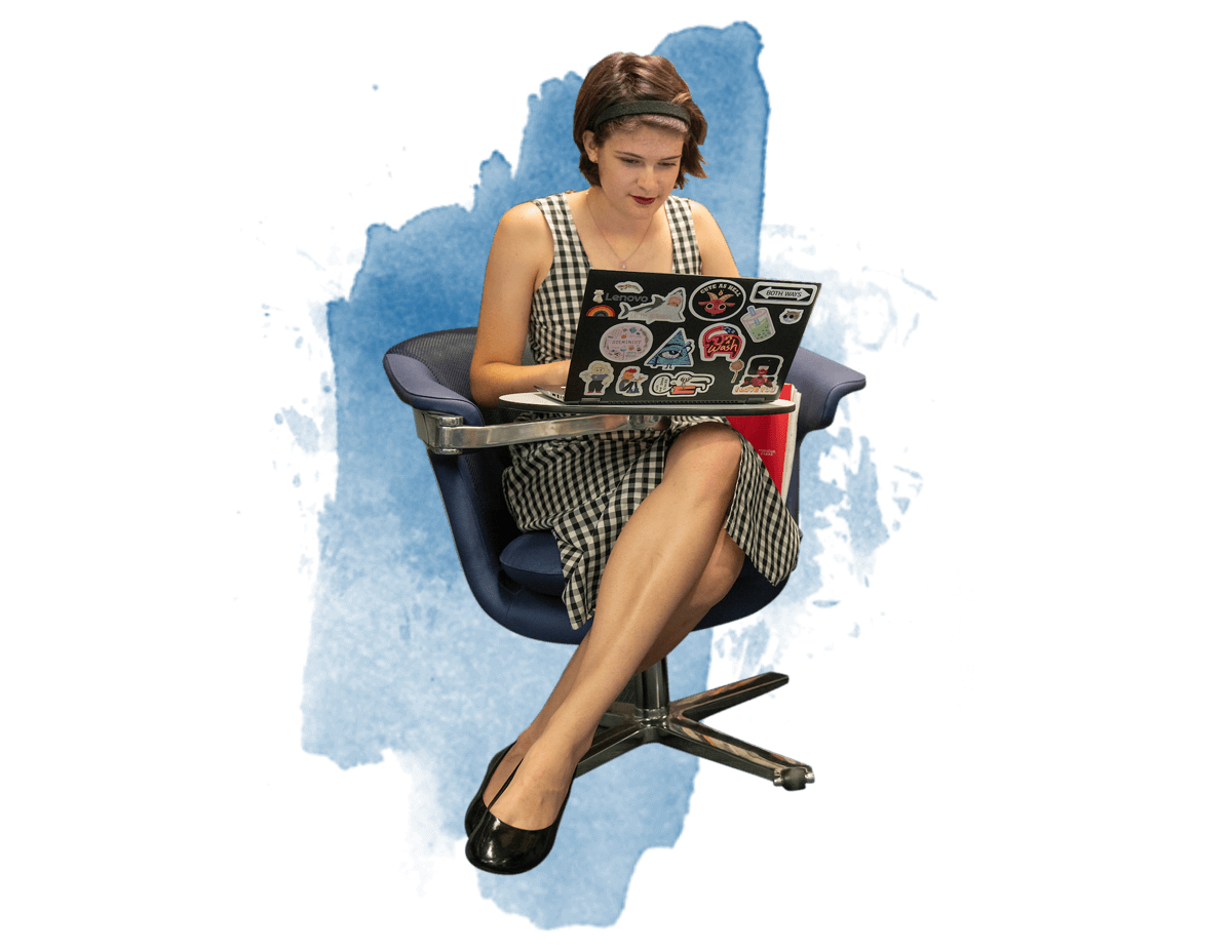 A female student sitting in a chair working on her laptop