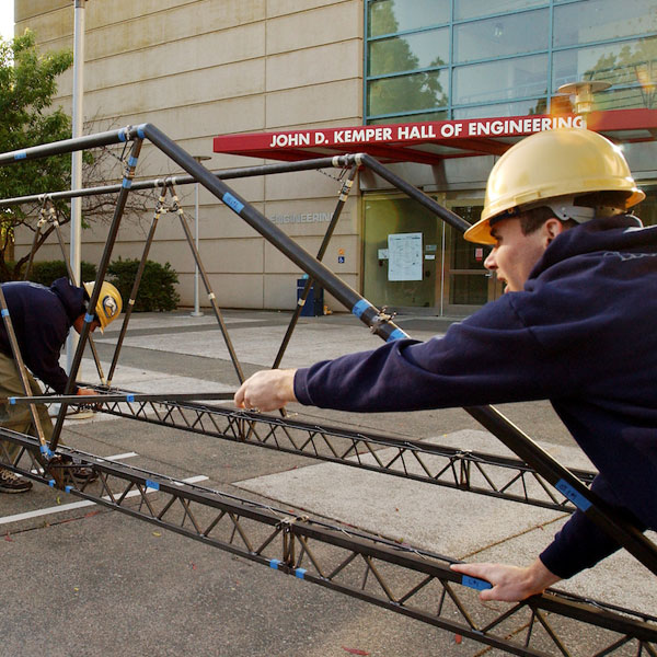 Students build an iron bridge outside of the Engineering complex at UC Davis