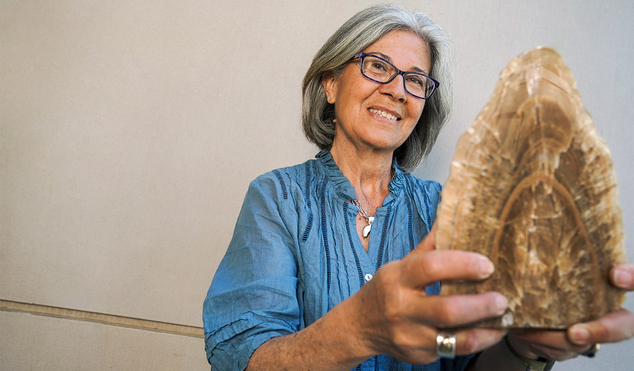 Woman holds fossil.