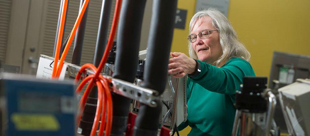 Linda works behind technical equipment and cords at UC Davis.