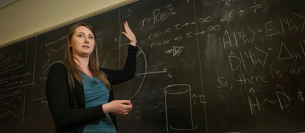Rachel stands in front of a chalkboard while lecturing at UC Davis