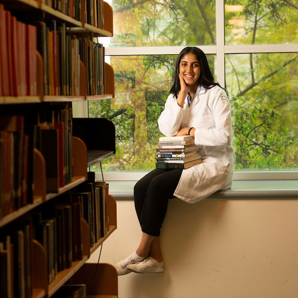 A medical student takes a break from her studies in the library