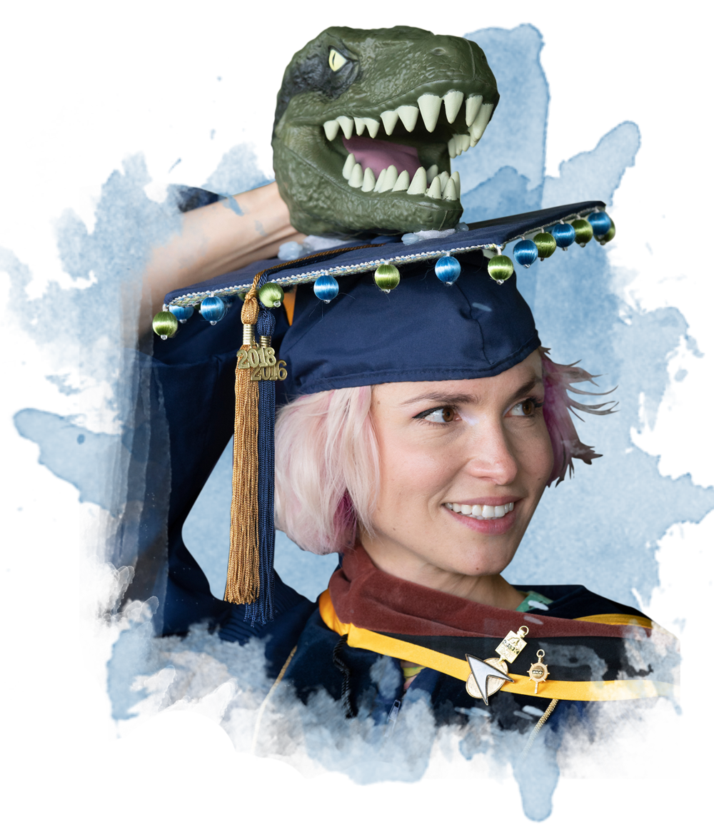 A student dressed for graduation with a t-rex head atop her grad cap