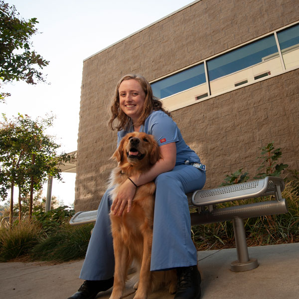 A veterinary student cares for a dog outside of the UC Davis School of Veterinary Medicine