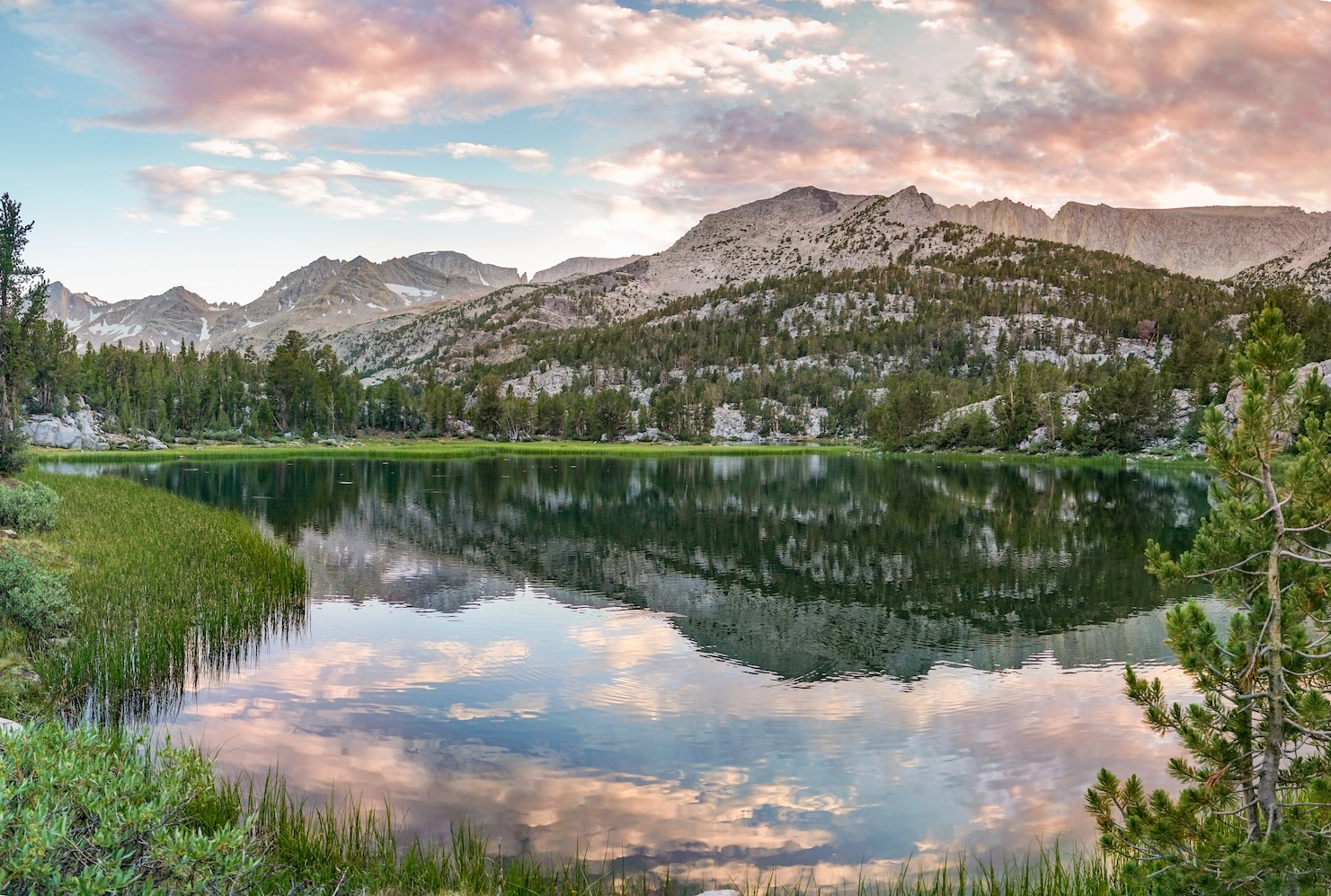 A sunset sky reflects in an alpine lake surrounded by pine trees and mountains in Sequoia and Kings Canyon National Park