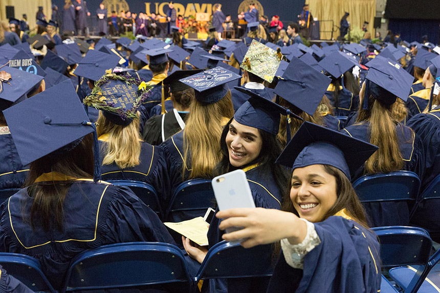 Graduating students take a selfie at commencement.