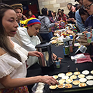 Students cook food for the International Student Fair.