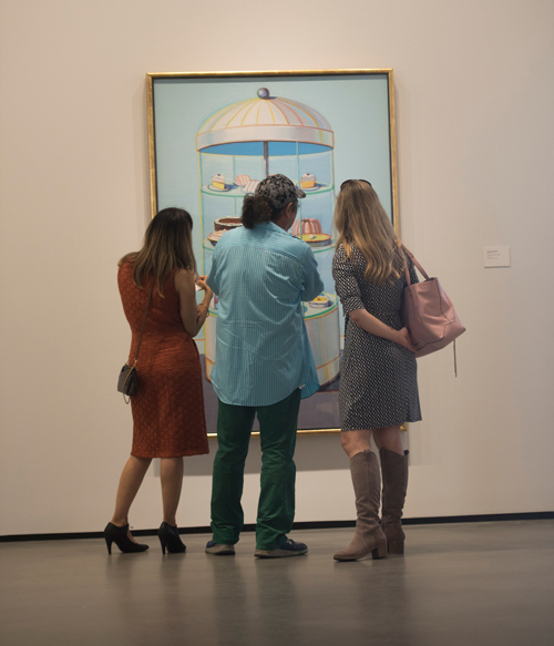 Three museum visitors gaze at a painting.