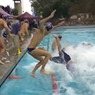 Water polo players and coaches jumping into a pool.