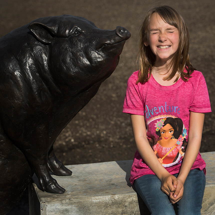 A young girl sits next to a pig statue.