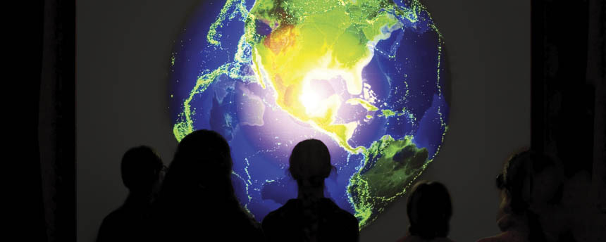 Viewers stand in front of a screen showing a digital image of the globe