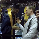 Two people shake hands at commencement