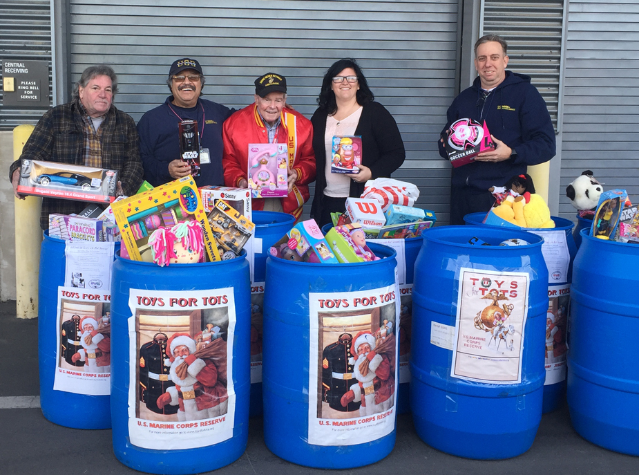 Five people stand behind Toys for Tots barrels filled with toys.