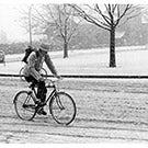 A bicyclist rides through the snow.