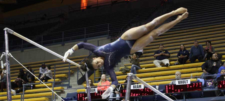 Alexis Brown in the air, while doing exercise on the uneven bars