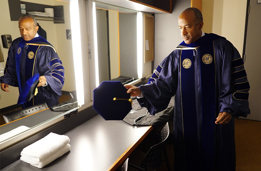 Gary S. May prepares backstage before the investiture.
