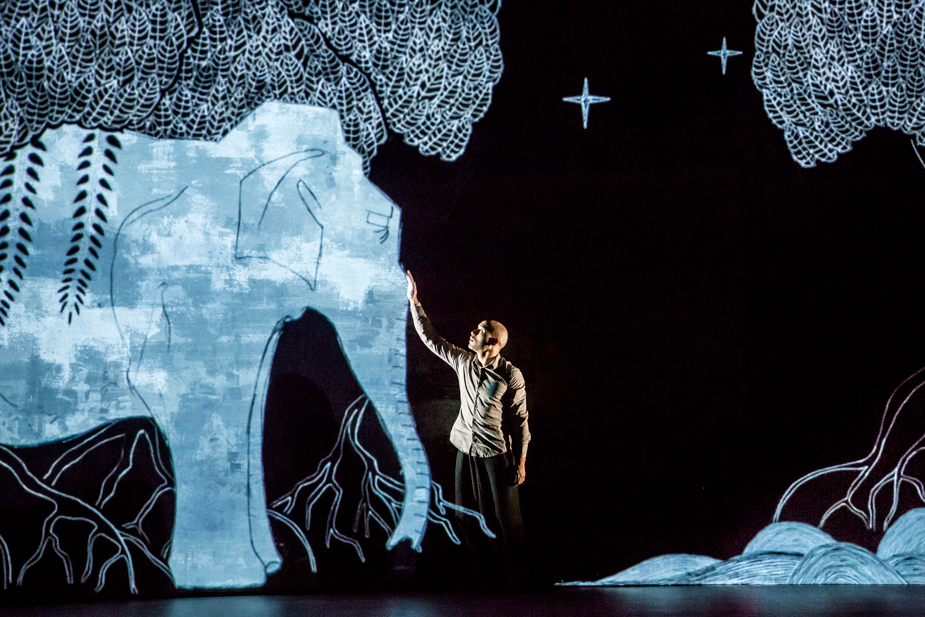 "Scene from Akram Khan dance company's ""Chotto Dash,"" showing a man touching an animated elephant."