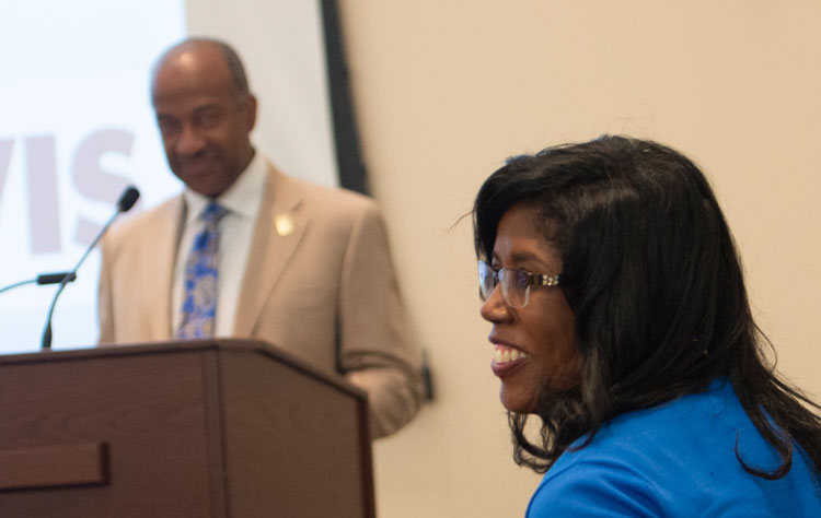 Sonja Colbert at meeting, with Chancellor May at podium, in the background