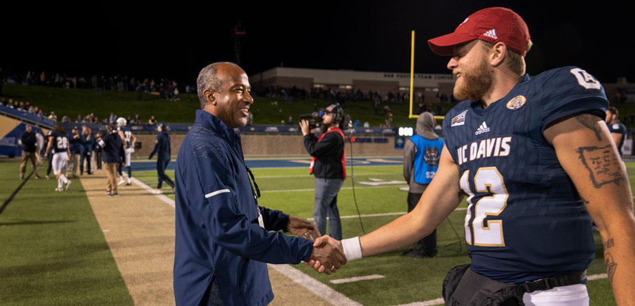 Chancellor May shakes hand of football player on sidelines.
