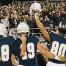 Football player holds up helmet, saluating the fans in the stadium.