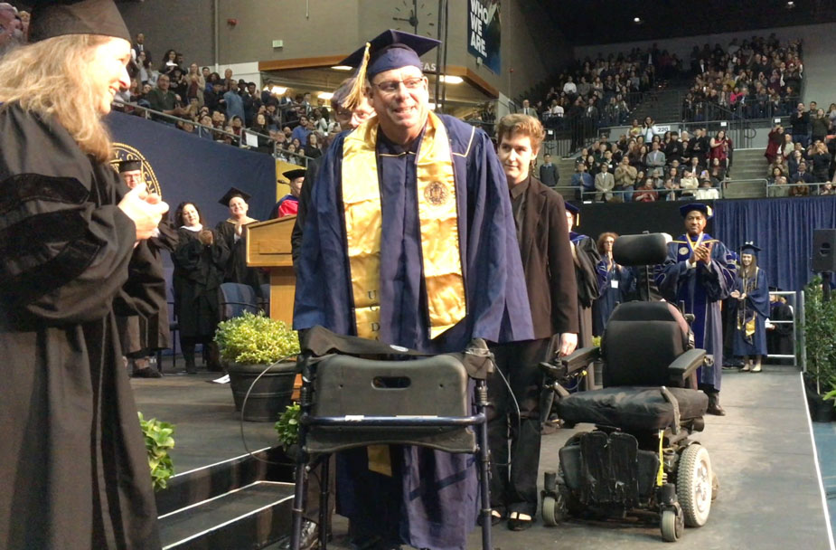 Michael O'Hearn in cap and gown, using walker.