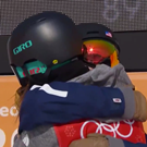 Two skiers embrace.