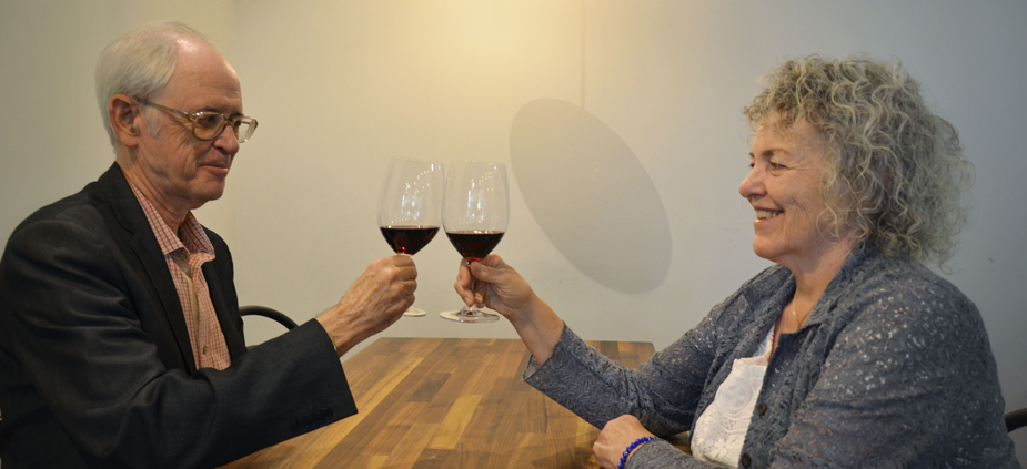 Two people toast across table, each holding a glass of wine.