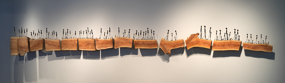 Bloodline sculpture, figures on wood platforms, as if walking across a wall