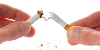 Cigarette between fingers, being broken in half