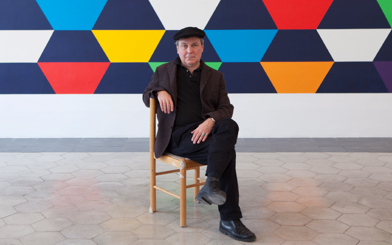 Stephen Westfall, seated in front of geometric painting