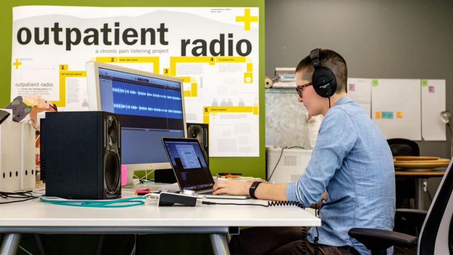 Tracy Manuel, headphones on, at computer screens -- working on radio program.