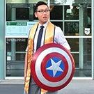 A graduating senior holding Captain America's shield.