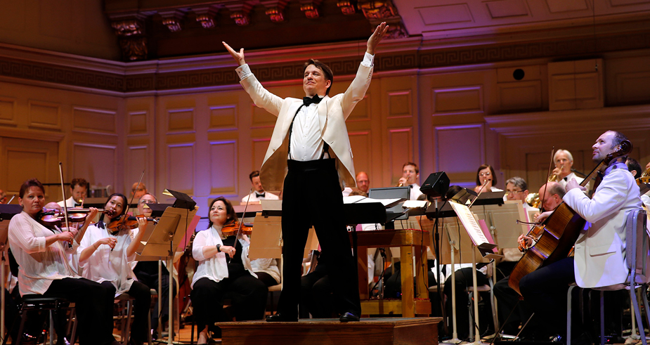 Keith Lockhart raises his arms in triumph, orchestra behind him