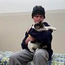 A boy holds a cat