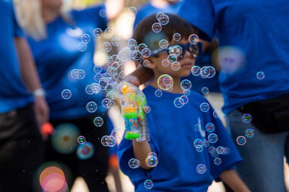 Boy blows bubbles in parade,