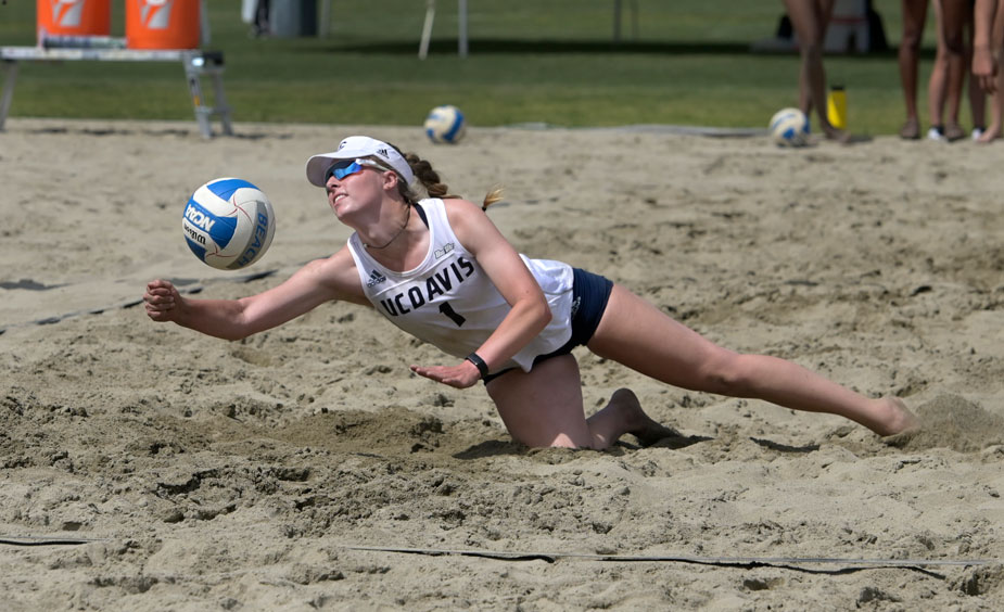 Player dives for ball in beach volleyball.