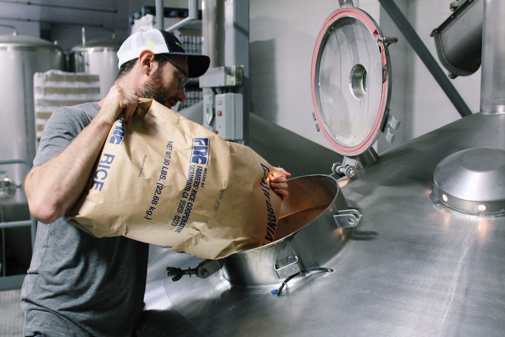Man pours large bag of rice into brewer.
