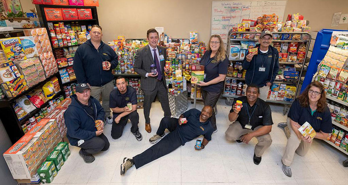 Mail Services personnel pose in front of donated food.