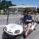 Dan Hawkins driving a golf cart.