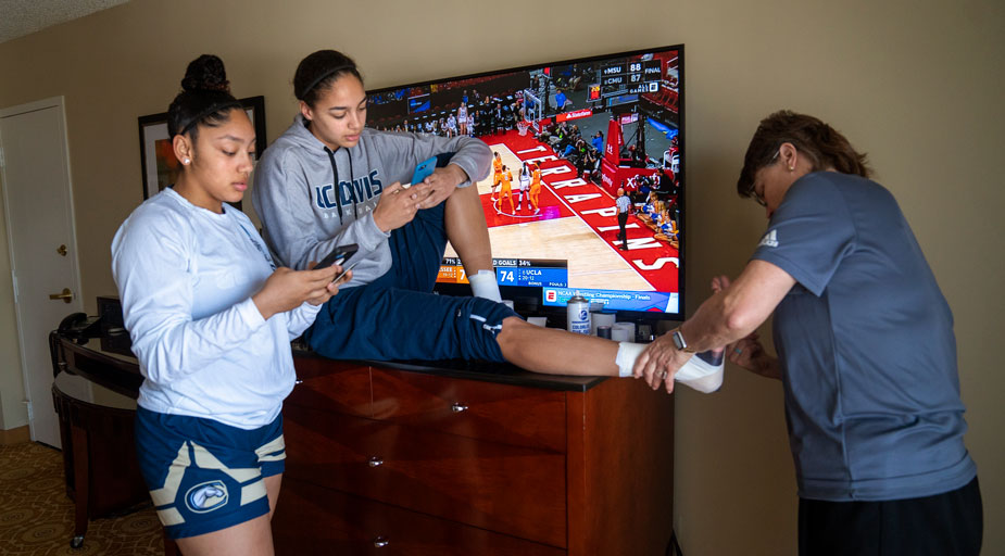Players on phones; one player is having her ankle taped by a trainer.