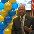 Chancellor May, seated, surrounded by blue and gold balloons.