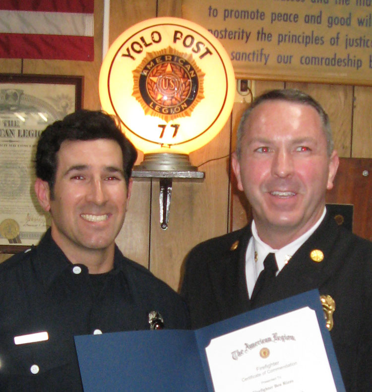 Fire chief presents certificate to firefighter.