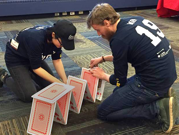 Students build house of cards with giant cards.
